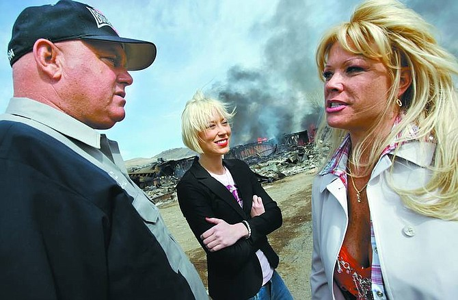 """Chad Lundquist/Nevada Appeal Moonlite BunnyRanch brothel owner Dennis Hof talks with two of his working girls Brooke Taylor, center, and a woman who identified herself as """"Air Force Amy,"""" right, as the remains of the former Mustang Ranch 2 brothel burns during a training exercise on Sunday."""