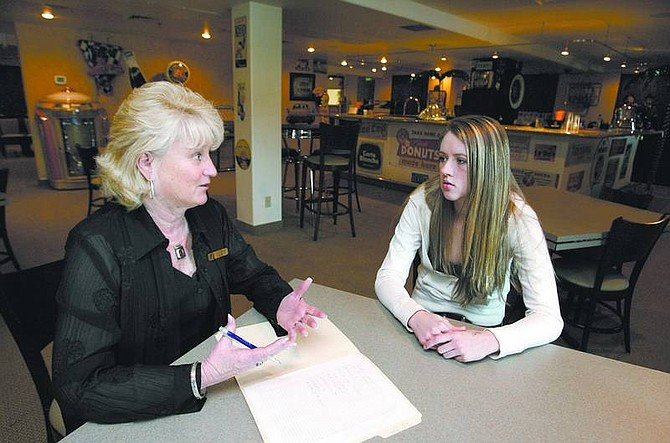 Cathleen Allison/Nevada Appeal Carson High School senior Lindsay Ford, 18, works with Terrie McNutt at Coaches banquet room at Silver Oak Golf Course on March 20. Ford's senior project is coordinating the Senior-Senior prom, which will be held at Coaches.