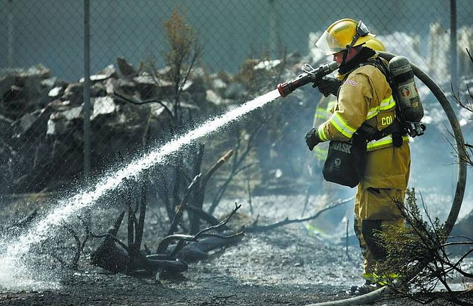 Chad Lundquist/Nevada Appeal A Carson City firefighter works to extinguish a brush fire at Villa Sierra mobile home park in the 4900 block of Highway 50 East on Monday. One home was damaged and one-quarter of an acre was burned.