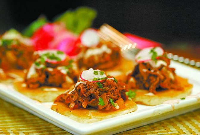 BRAD HORN/Nevada Appeal Brain Shaw, of Cafe del Rio, make pupusas, little masa cakes with potato and cheese, and tops them with beef picadillo - Spanish seasoned beef with almonds and raisins.