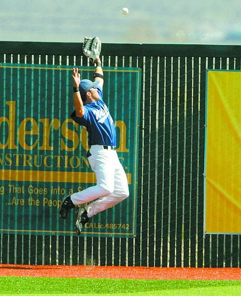 BRAD HORN/Nevada Appeal WNCC's Pat Grennan reaches for a home run ball at John L. Harvey Field on Friday.