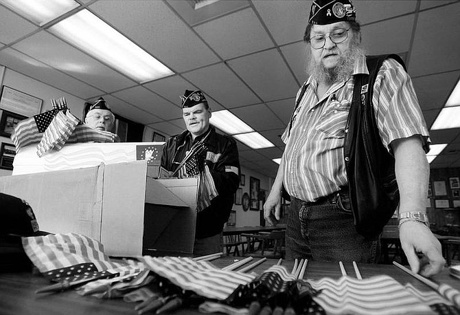 Disabled American Veterans members James E. Billig, Jr., left, Commander Les Laberee, center, Wayne Willson, right, all Carson City Chapter 7 members, look through some of the American flags that will be placed on graves of veterans at Lone Mountain Cemetery.  Chad Lundquist /Nevada Appeal