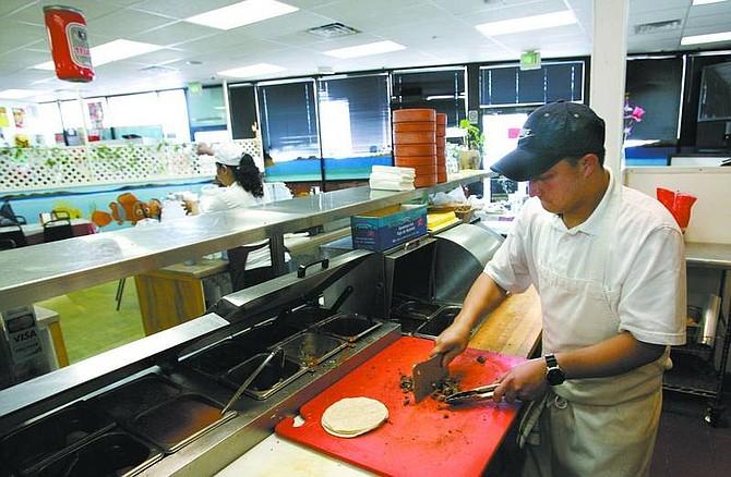 Cathleen Allison/Nevada Appeal Alonso Castellanos prepares tacos Thursday at Capital City Dos Amigos.