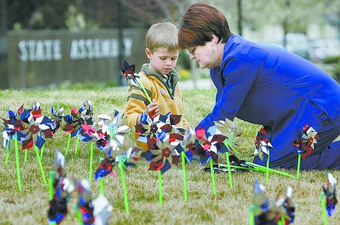 Cathleen Allison/Nevada Appeal Mary Liveratti, with Carson City Health and Human Services, helps Kellen George, 5, place pinwheels on the Legislative lawn Thursday morning. Child advocates planted the pinwheels in recognition of Child Abuse Prevention Month, placing 422 pinwheels, one for each case of child abuse that was reported in Carson City in 2006.