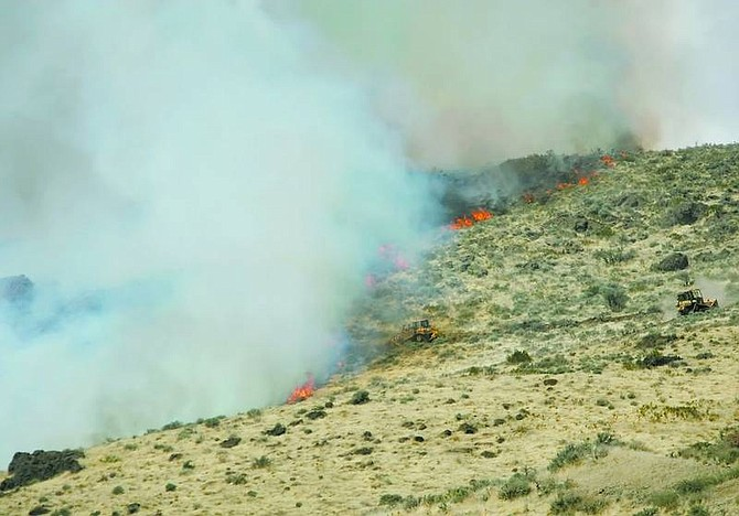 BRAD HORN/Nevada Appeal Bulldozers build a fire line at the top of a hill in Pleasant Valley to help combat a brush fire that burned about 75 acres Friday morning. Officials said they hoped to have the fire contained by the end of the day.