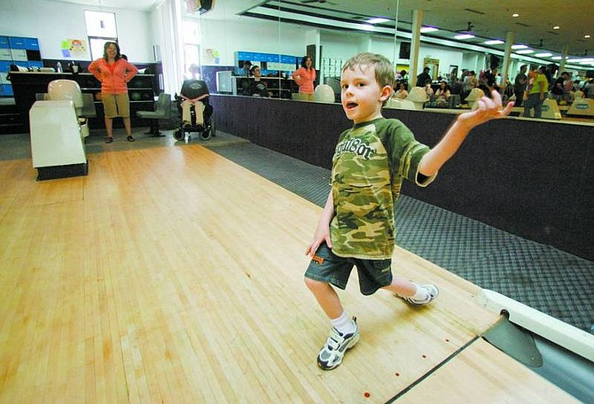 BRAD HORN/Nevada Appeal Quinn Rondeau, 5, of Virginia City, celebrates a spare on Saturday at the Carson Lanes. His brother Jacob, back, and mother Jenna were celebrating Jacob's 20th birthday at the event.