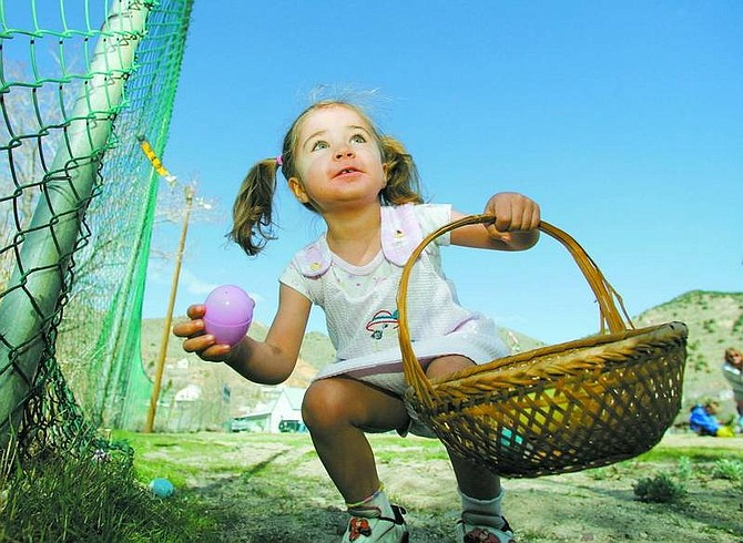 BRAD HORN/Nevada Appeal Norissa Lockhart, 3, of South Lake Tahoe, finds her first egg during her first Easter Egg hunt during the Great Virginia City Easter Egg Hunt on Saturday at Miner's Park.