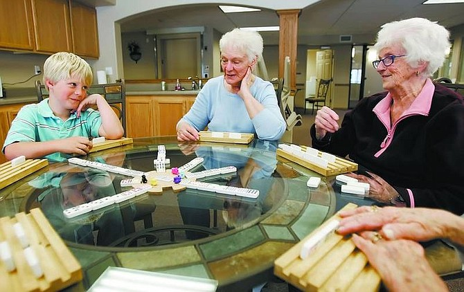 Connor Brown, 7, plays Mexican train with Flo Hobdy and Wilma Dunn at Autumn Village on Monday afternoon. Autumn Village Phase 1 is an affordable senior housing project that was completed in September. Phase II is under construction and should be completed by late July.    Chad Lundquist/ Nevada Appeal