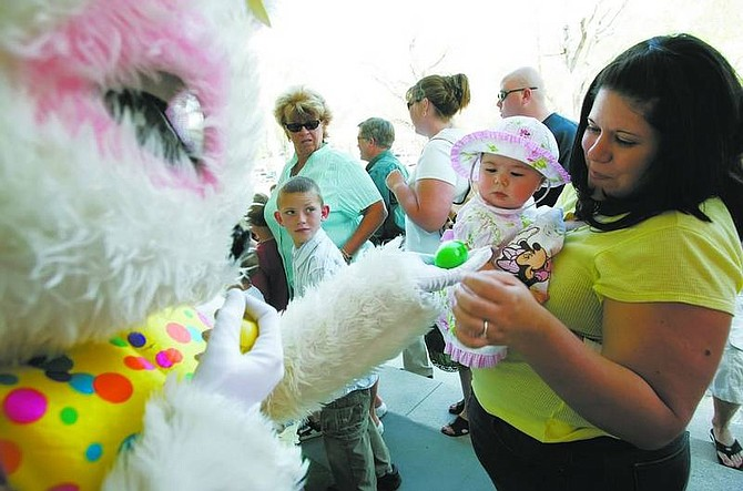 Eight-month-old Stacy Croteau, center, with help from mom Mandy, is handed her first Easter egg by the Easter Bunny on Sunday. More than 3,000 children celebrated Easter at the Governor's Mansion.  Chad Lundquist/ Nevada Appeal