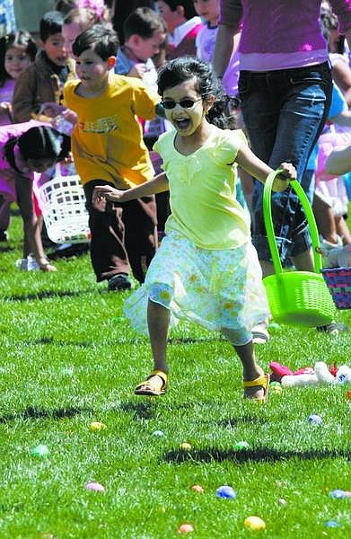 Chad Lundquist/Nevada Appeal Aishwarya Anand, 5, dashes forward to collect her share of the 20,000 brightly colored Easter eggs placed on Governor's Field Sunday afternoon. It only took four minutes for the 3,500 children to gather what took volunteers more than an hour to disperse.