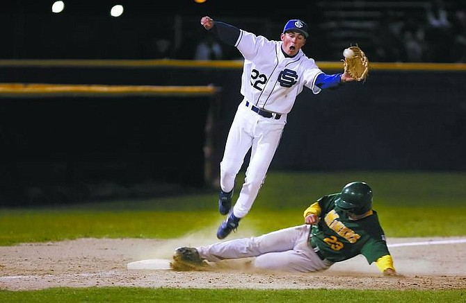 Chad Lundquist/Nevada AppealCarson's (22) Bryt Lewis jumps into the air while attempting to keep Manogue's (23) Craig Batory from stealing 3rd base during Tuesday nights game.