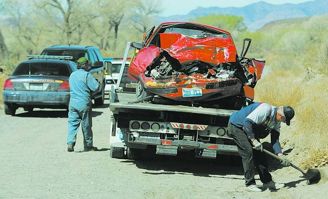 BRAD HORN/Nevada Appeal A tow truck driver gets ready to transport the red Ford Mustang that was involved in a two-car accident on Fort Churchill Road in Silver Springs on Friday morning. A 17-year-old boy was killed, and four other teens were taken to the hospital.