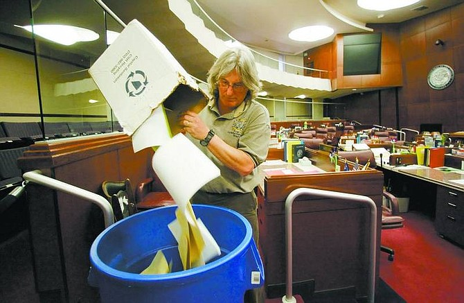 Mike      Hoffman dumps dead bills and other trash into a  trash can in the Assembly Chambers at the Nevada State      Legislature on Friday.  Brad Horn/ Nevada Appeal