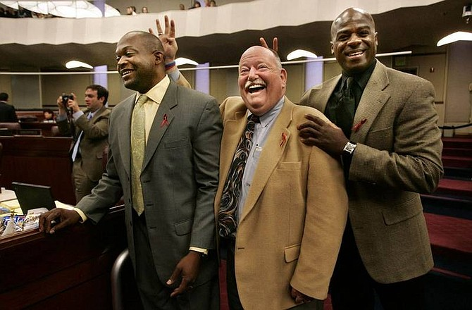 Cathleen Allison/Nevada Appeal  Nevada Assemblymen, Bernie Anderson, D-Reno, center and Kelvin Atkinson, D-North Las Vegas, right, help Assemblyman William Horne, D-Las Vegas, as he tries to give a media interview Friday afternoon on the Assembly floor at the Legislature.