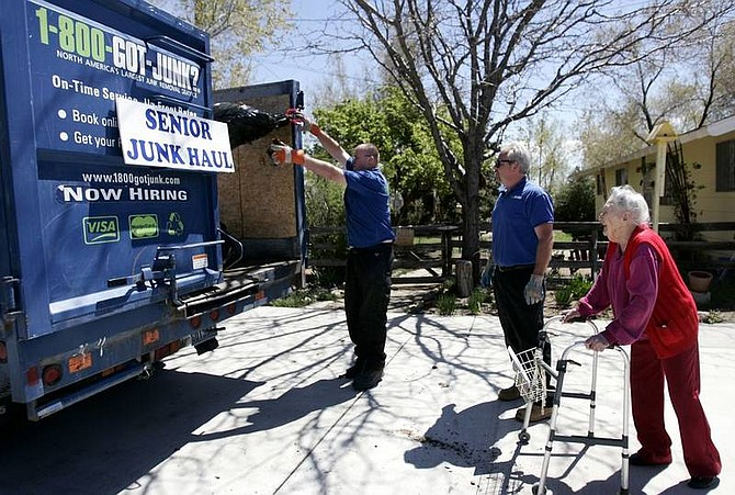 Chad Lundquist/Nevada Appeal Esther Humphrey, 97, watches as David Bouino and Mark Johnston from 1-800-Got-Junk?, pick-up yard trimmings from her home in North Carson City on Monday. The company is providing free service to elderly and disabled people as part of Carson Pride Week.