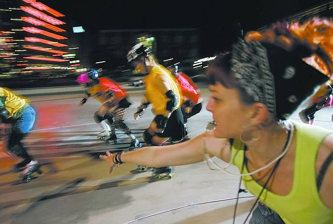 """Chad Lundquist/Nevada Appeal Kristina Tarleton, aka """"Sailor Doom,"""" coach for the Battle Born Derby Demons pushes her girls during practice in downtown Reno on Tuesday night. The team has scheduled its first contest set for May 19 against a team from Utah at a site to be determined in Reno."""
