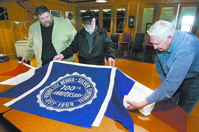 Cathleen Allison/Nevada Appeal From left, Comstock Historic District administrator Bert Bedeau, Chic DiFrancia and Doug Klawsnik look at a historic Virginia City banner Tuesday. Nearly 50 years ago the banner was swiped by Klawsnik and a friend during the 100-year celebration. The theft likely led to the banner's salvation. It's new home will be with the Comstock History Center.