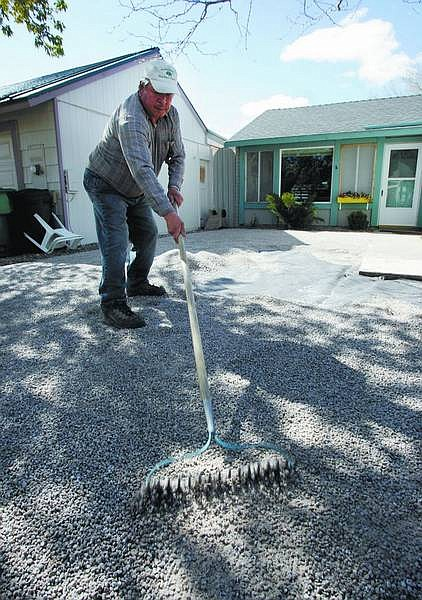 Chad Lundquist/Nevada Appeal Villagrana, an employee for Green House Garden Center, works to smooth gravel in a Japanese-style garden being installed as an alternative to a lawn.