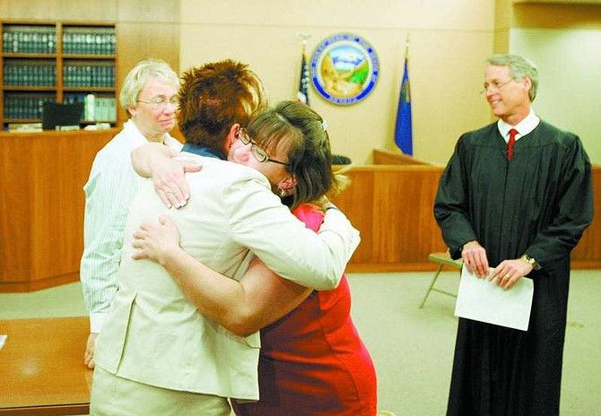 BRAD HORN/Nevada Appeal Marie Saxon hugs mental health director Lisa Treinan while Judge John Tatro looks on after Sexon graduated from the program on Wednesday. Sexon has been clean from all drugs for more than a year, after battling a 20-year drug addiction.
