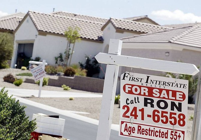 """Isaac Brekken/Associated Press """"For sale"""" signs hang in front of homes on Cumberland Hill Drive in Henderson, outside Las Vegas on Tuesday."""