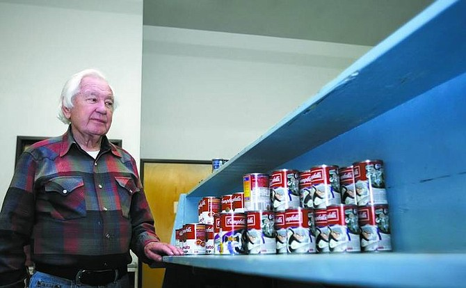 Chad Lundquist/Nevada Appeal FISH Food Pantry Manager Jim McMullen looks over mostly empty pantry shelves Wednesday afternoon. FISH is one of the recipients of Saturday's Stamp Out Hunger food drive by the National Association of Letter Carriers.
