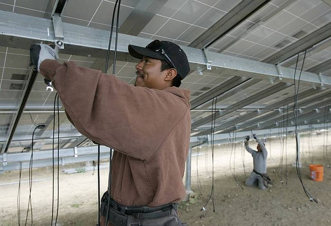 Eric Risberg/Associated Press Workers install wiring below newly-installed solar panels at the Far Niente winery in Oakville, Calif., on Sept. 18.