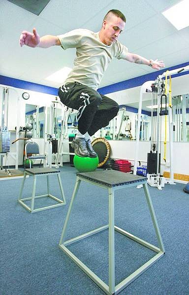 Peden demonstrates hops. McEwan stresses that skiers can start with small heights and work their way up. Any kind of riser can be used at almost any height, working up to higher leaps. The ball is in the background, not under his feet.