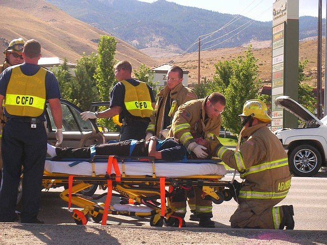 Carson City paramedics treat a young woman injured in an accident at Carson and Colorado streets this afternoon