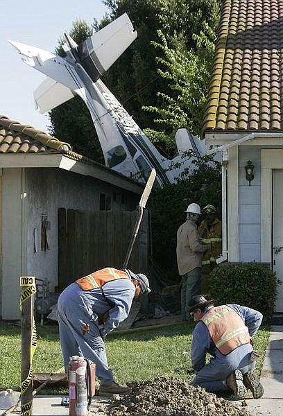 Utility crews shut off the natural gas flow to a home where a plane crashed into it in Compton, Calif. on Saturday, April 12, 2008. A small airplane crashed into a home several blocks from the Compton Airport injuring five people, three on the ground and two from the aircraft. Four of the victims were reported to be in critical condition. (AP Photo/Dan Steinberg)