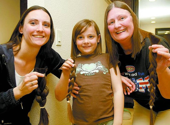 Michelle Van Geel, Nicole Van Geel, 7, and Regina Erb with their ponytails on March 11 at C & Company.  Shannon Litz/Nevada Appeal News Service