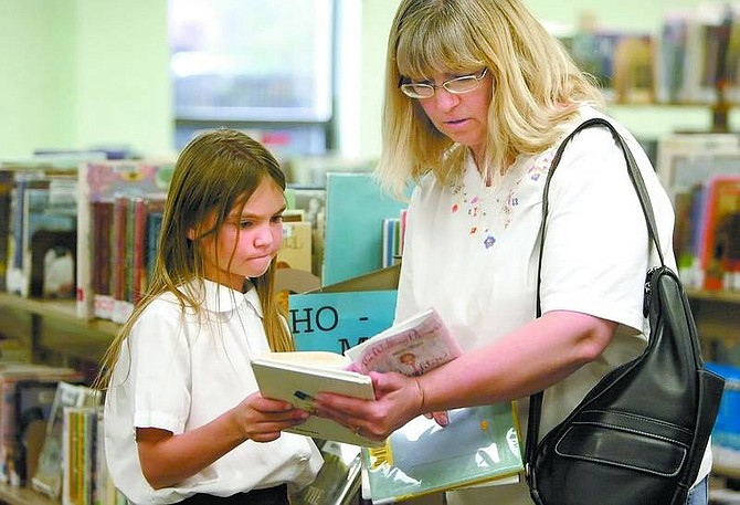 Amy Lisenbe/Nevada Appeal Shelby Jones, 7, and her mother Karla review some of the books they selected from the shelves in the youth area of the Carson City Public Library to decide what they will check out Monday afternoon.