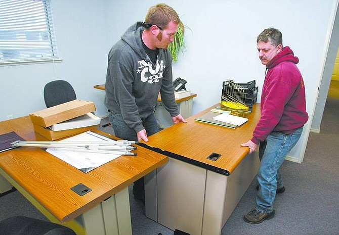 Cathleen Allison/Nevada Appeal Former Citizens for Affordable Housing staff members Eric Machado, left, and Nick Tolotti arrange their new office Thursday afternoon in Carson City. Nevada Rural Housing Authority has applied to administer the program.