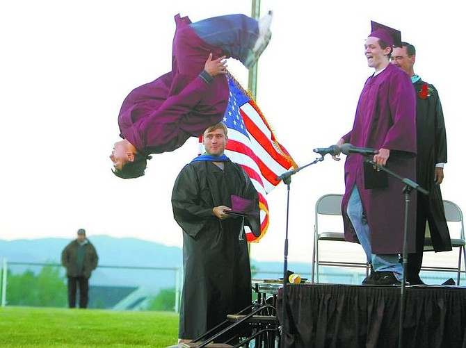 BRAD HORN/Nevada Appeal Dayton's Justin Benitez does a backflip after receiving his diploma while his basketball coach T.W. Cunningham, in front of flag, watches on Thursday.