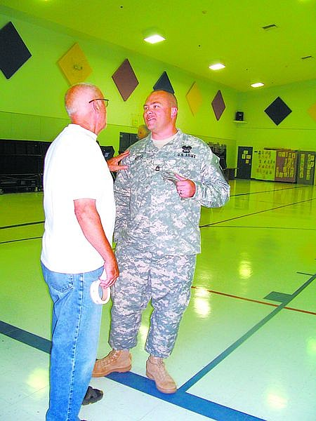 Karen Woodmansee/Nevada AppealPoll worker Chuck Beal talks to 1st Sgt. Harry House after House cast his vote Tuesday at Sutro Elementary School in Dayton.