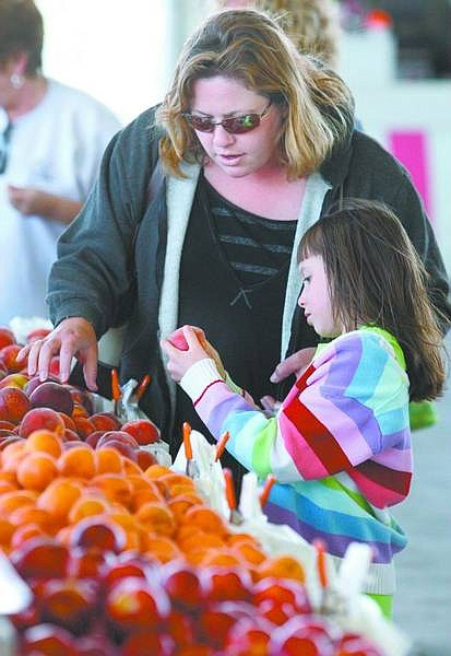 Cathleen Allison/Nevada Appeal Sarah Sorich, 7, helps her mom Renee choose peaches Wednesday afternoon at the first Carson City Farmer's Market of the season. The market is open 3:30 p.m. - 7:30 p.m. on Wednesdays at the Pony Express Pavillion in Mills Park.