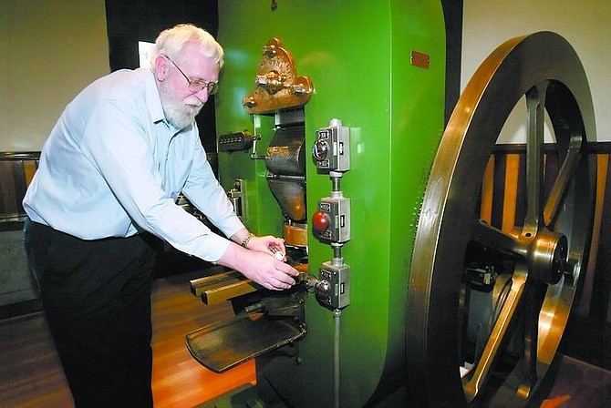LEFT: Bob Nylen, curator at the Nevada State Museum, explains how Carson City Mint's Coin Press No. 1 operates at the museum on Monday. Nylen will give a lecture at 7:30 p.m. today on Abraham Curry, the Carson City Mint's first director, as part of celebrating National Coin Week.   Below: Nylen holds a .999 fine silver medallion design of the Carson City Mint's first coin struck. The museum's collection of Carson City mint coins feature 109 of 111 coins that make up the entire set.     Amy Lisenbe/Nevada Appeal