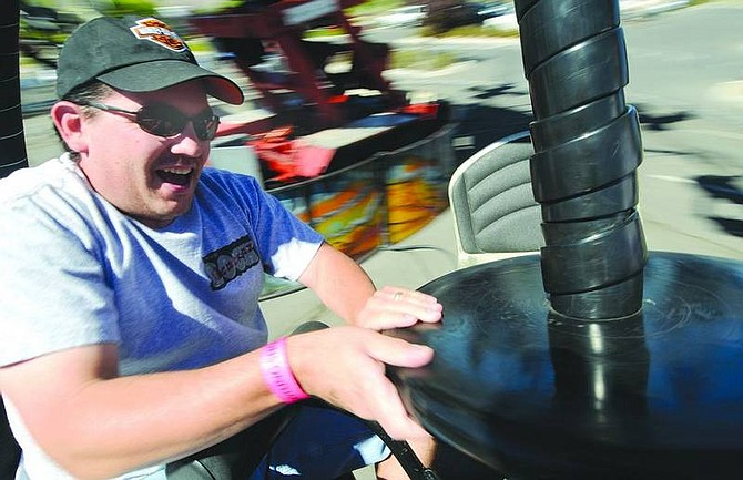 Kevin Clifford/Nevada Appeal Scott Wilde of Dayton spins the seat while riding the Tornado with his wife Staci Wilde, not pictured, during the Carnival at Dayton Valley Golf & Country Club on Saturday. Seventy-five percent of the proceeds from the four day event go to Carson Advocates for Cancer Care.