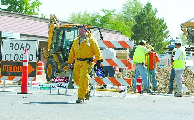 BRAD HORN/Nevada Appeal A Southwest Gas employee walks through the intersection at Fairview Drive and Roop Street after a gas pipe broke while workers were repairing the street on Monday afternoon. The pipe was repaired shortly thereafter, and no one was hurt in the incident.