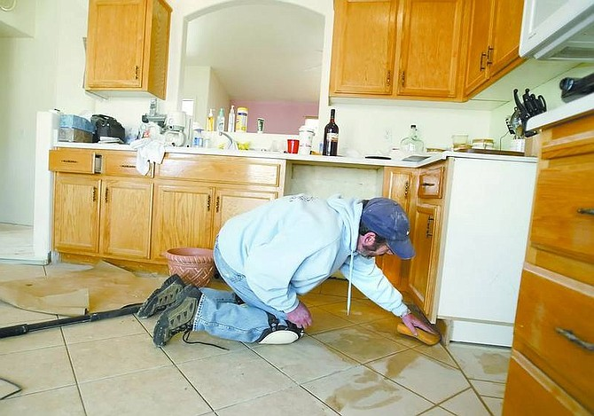 Amy Lisenbe/Nevada Appeal Fernley resident Wesley McKnight washes excess grout from newly laid tile in the kitchen Monday afternoon, one of many efforts the home owners have made to repair flood damage to their home on Jenny's Lane.