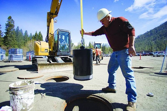 Jonah M. Kessel / Nevada Appeal News Service Jim Tigue of C.B. Ebright helps lower a filter cartridge into a stormwater treatment vault in the parking lot of Heavenly Mountain Resort's California Base Lodge.