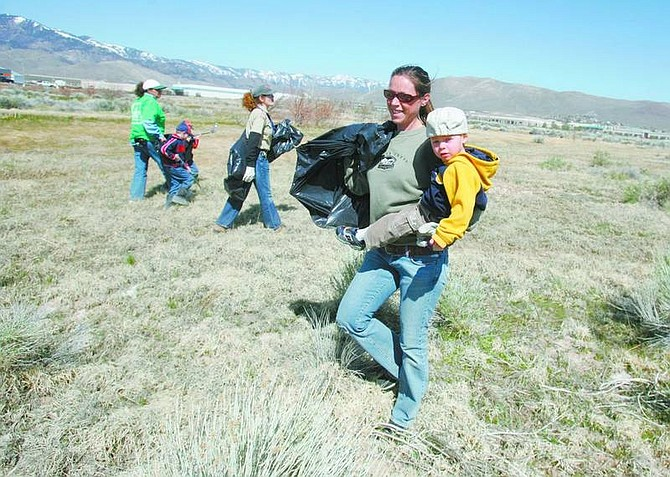 Kim Borgna carries her son Connor, 2, of Reno, during a cleanup event in advance of Earth Day in the wetlands area behind St. Teresa of Avila Catholic Church on Saturday.  BRAD HORN/Nevada Appeal