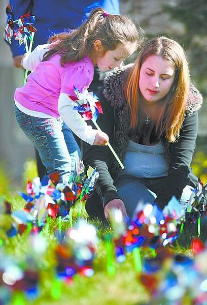 Cathleen Allison/Nevada AppealCarson High School senior Alexandra Mercer helps Rebekah Rhea, 5, place pinwheels on the Legislative lawn Tuesday afternoon as part of Child Abuse Awareness Month. The 492 pinwheels represent investigated cases of child abuse in Carson City in 2007.