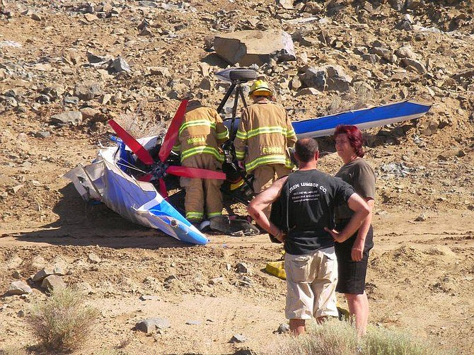 The unnamed instructor and pilot of a light aircraft talk near the wreckage at the Carson City Airport this morning. The pilot, who was practicing landings, was uninjured.
