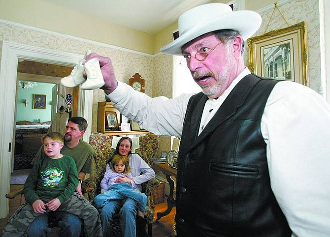 Amy Lisenbe/Nevada Appeal Hank Monk, portrayed by Fred Stanio, auctions off a pair of bootees received as a birthday gift. The Sunday afternoon auction at the Olcovich-Meyers House was a birthday celebration with the Carson City Historical Society for stagecoach driver Hank Monk. Stanio as Hank Monk, also told stories about his life as a stagecoach driver. Auctioned items will benefit the Carriage House.