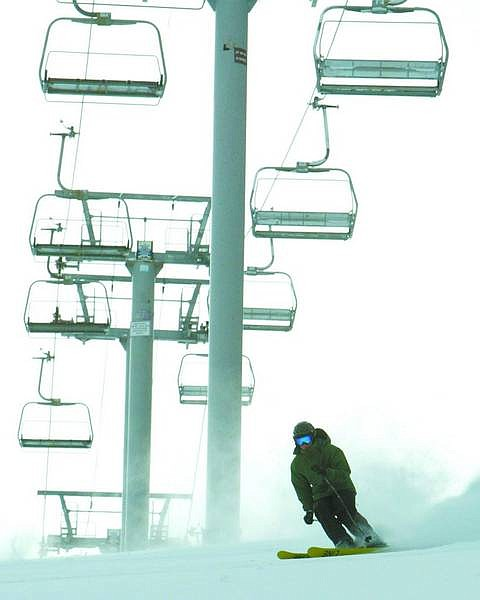 Jim Grant / Nevada Appeal News Service Stephen Austin, a Sierra-at-Tahoe season passholder who was picked at random for the resort's Early Load Program, skis under the riderless West Bowl Express chairlift Wednesday morning.