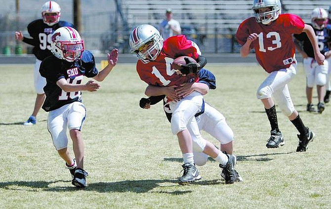 Amy Lisenbe/Nevada Appeal Ohio State Buckeye's Bailey Vidaurri, center, carries the ball as he is met by Anthony Sparks, left, and Anthony Alioto, tackle, of the SMU Mustangs Sunday afternoon during a football Scholars and Champions Jamboree at the Carson High football stadium.