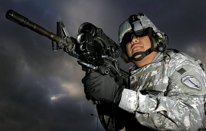 U.S. Army Staff Sergeant Ruben Romero, from Fort Benning, Ga., demonstrates new technology making use of a magnifying video camera and thermal imaging on the M4 weapon, during a demonstration on the sidelines of a NATO summit in Riga in November 2006.    Kirsty Wigglesworth/Associated Press