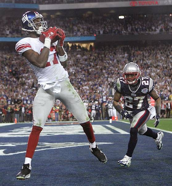 New York Giants receiver Plaxico Burress,left, grabs the game winning TD pass as New England Patriots defender Ellis Hobbs III trails the play in the end zone during 4th quarter NFL action in Super Bowl XLII, in Glendale, Ariz. on Feb. 3, 2008. (AP Photo/The Arizona Republic, David Kadlubowski) ** NO SALES ** NO MAGS ** MARICOPA COUNTY OUT ** MESA TRIBUNE OUT **