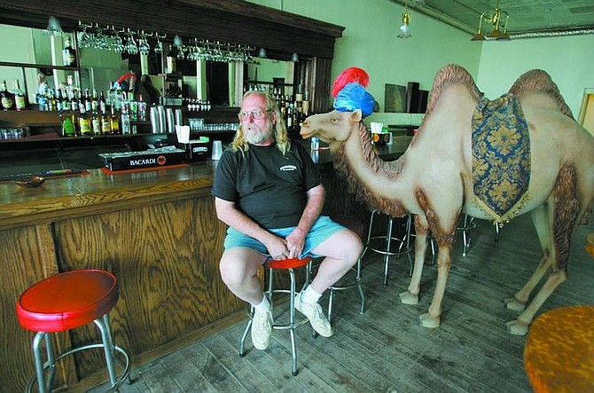 BRAD HORN/Nevada Appeal Gary Jackson, co-owner of the Kitty's Longbranch Saloon in Virginia City, poses near a plastic camel at his bar on Friday. The saloon was formerly known as the Red Dog Saloon. TOP: The Crosby Co., Girardo buildings, Comstock House, Masonic Hall and Comstock Assay Office group on northwest C Street in Virginia City are shown in this photo courtesy of Comstock Historic District. The Masonic Hall is gone now. The first floor of the Comstock House may be best known as The Red Dog Saloon, but it didn't take that moniker for almost 30 years after this Walt Mulcahy photo was taken in the mid-1930s.