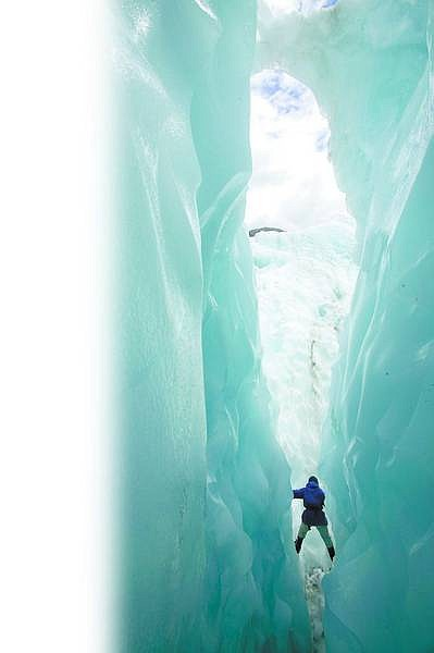 A climber moves through one of the ice caves on Franz Josef Glacier.